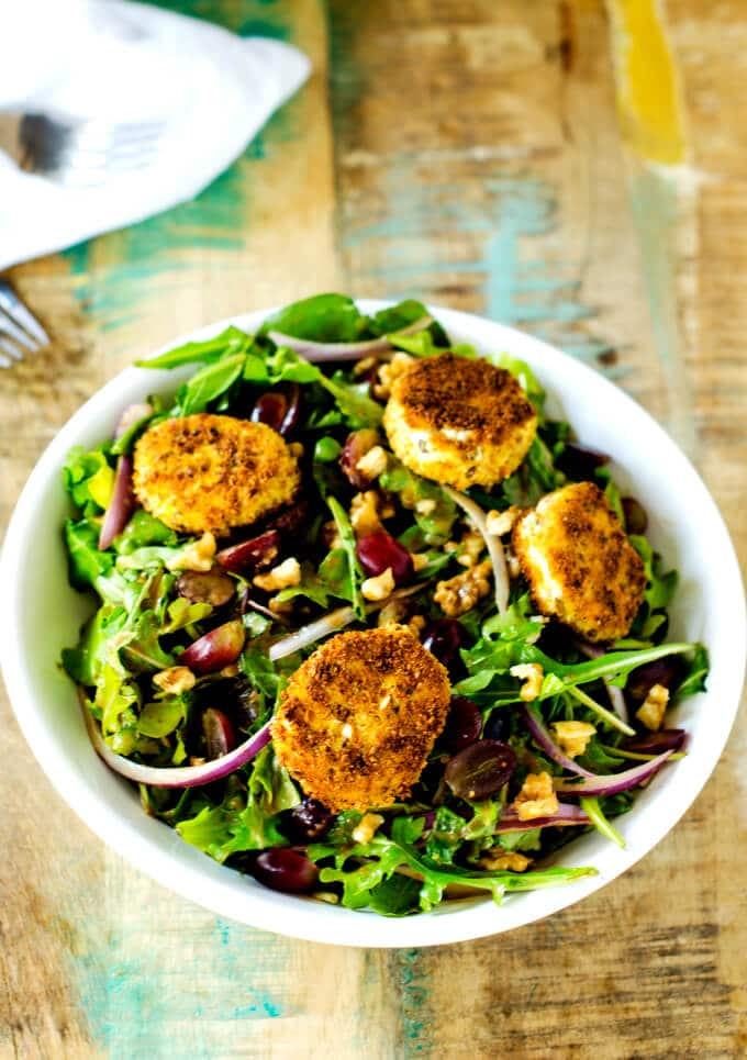 Shot of Fried Goat Cheese Salad with Grapes and Walnuts on a rustic background