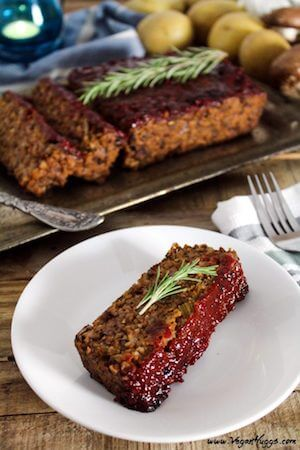 Photo os a Mushroom Walnut Meatless Loaf slice on a white plate with the loaf sitting behind it.