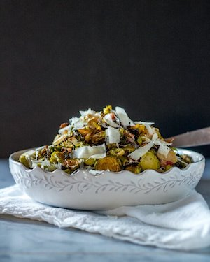 Photo of shredded Roasted Brussels Sprouts in a white bowl against a dark background.