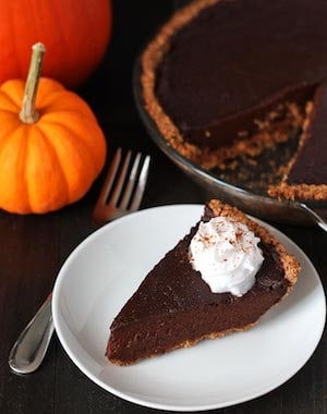 Photo of Vegan Chocolate Pumpkin Pie on a white plate against a dark background.