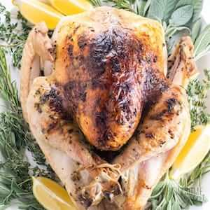 Photo of Whole Roasted Turkey on a serving platter garnished with herbs.