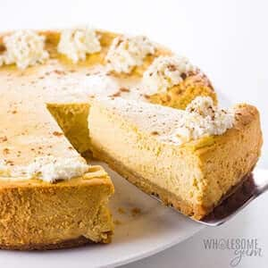 Photo of low carb Pumpkin Cheesecake in a white pie plate against a white background.