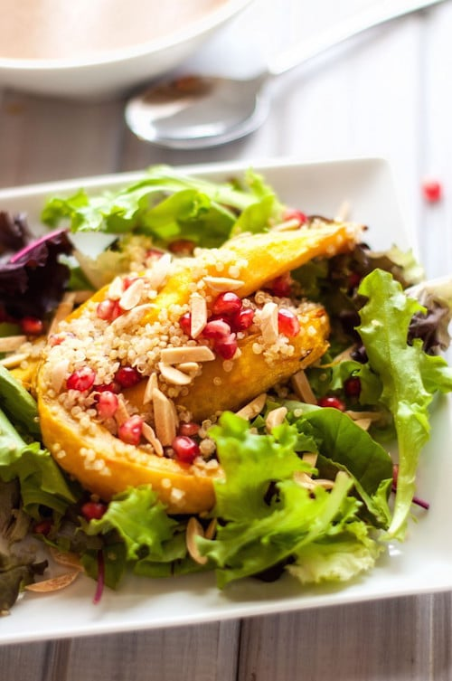 Photo of an Acorn Squash and Pomegranate Quinoa Salad on a square salad plate.