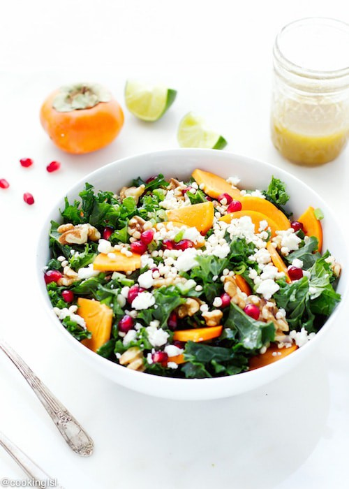 Photo of a Kale Salad with Pomegranates in a white bowl against a white background.