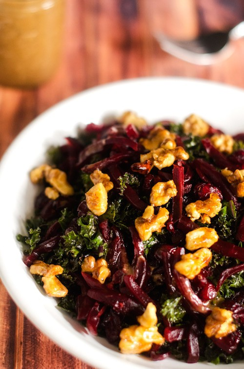 Photo of a Walnut Kale Beet Salad in a white salad bowl against a dark background.