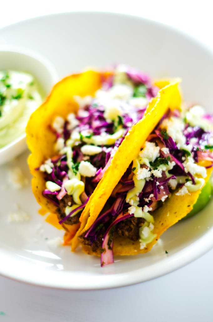 Beef Tacos with Cilantro Slaw and Avocado Dressing - These beef tacos are packed with flavor. The slaw has a nice kick to it that is perfectly offset by the cool avocado dressing. Naturally gluten free with dairy free and vegan options. - WendyPolisi.com