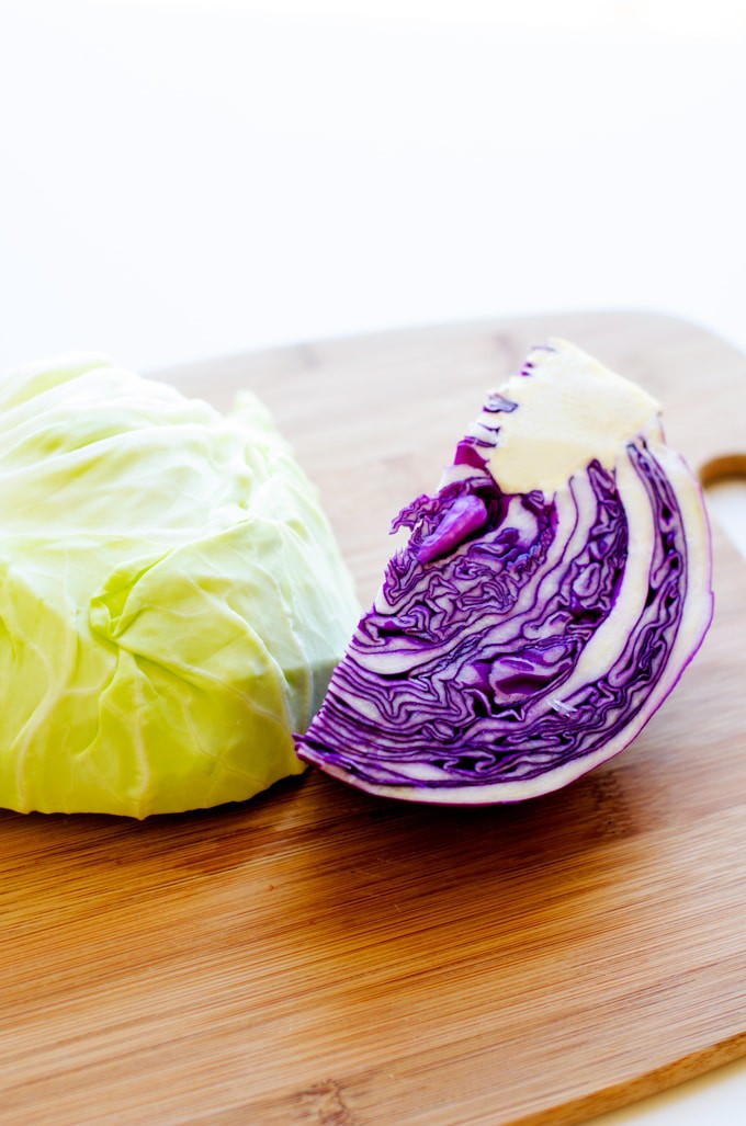 Photo of red cabbage and white cabbage on a cutting board against a white background.
