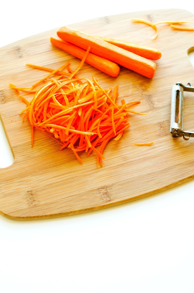 Photo of peeled carrots, a vegtable peeler, and shredded carrots on a cutting board.