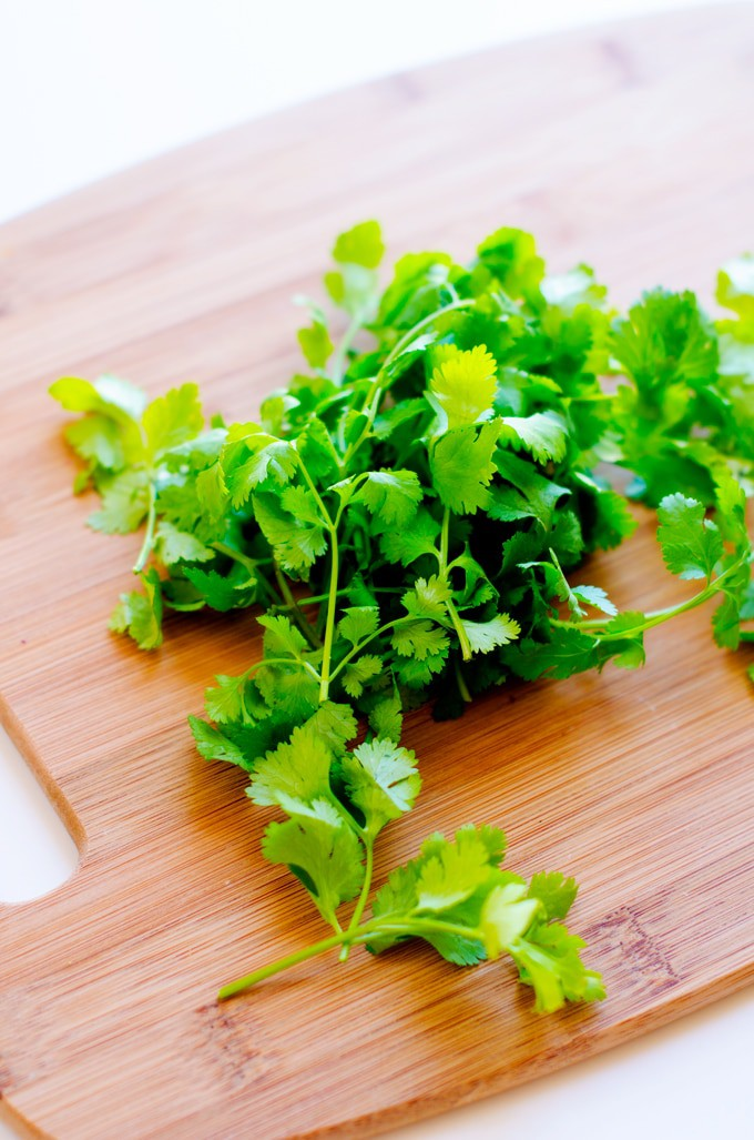 Photo of cilantro on a wooden cutting board.