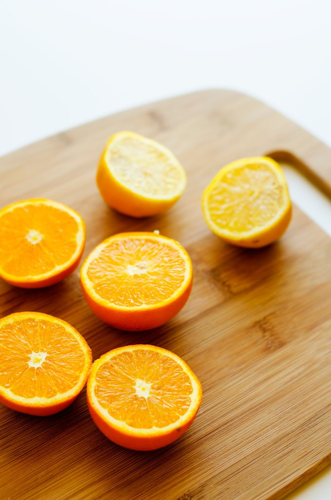Photo of halved oranges on a wooden cutting board.