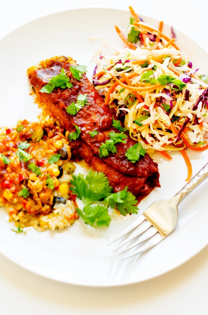 Photo of citrus slaw with an enchilada and corn side dish on a white plate.
