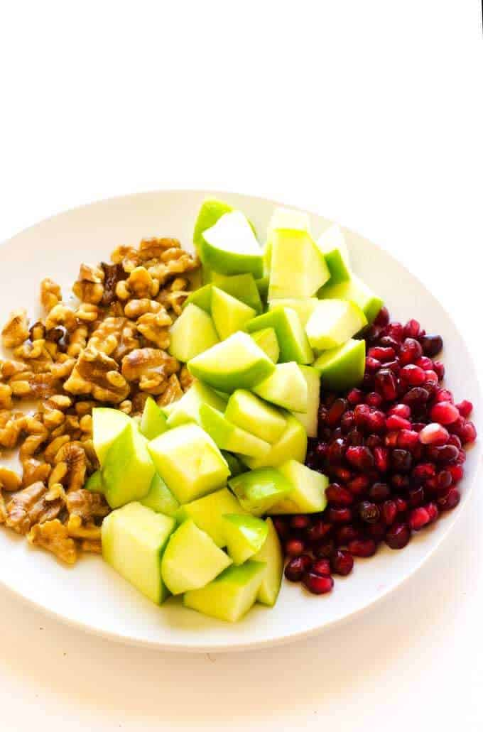 Photograph of chopped walnuts, diced apples and pomegranate ariels on a white plate.