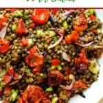 Photo of a lentil salad on a white plate with the text Roasted Garlic & Tomato Lentil Salad above.