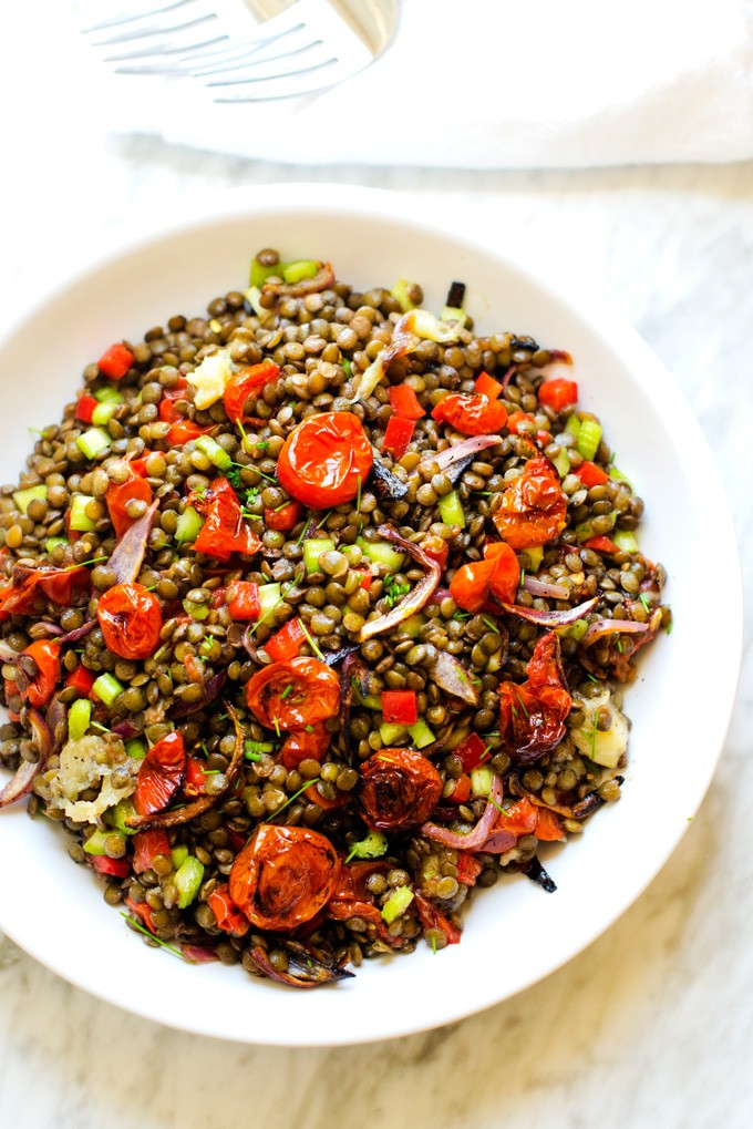 Photo of a lentil salad with roasted tomatoes, onions, and garlic in a white serving dish sitting on a white marble background.