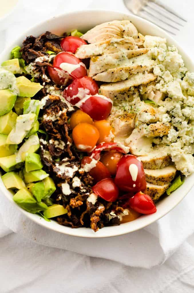Overhead photo of a Avocado Grilled Chicken Salad in a white bowl drizzled with a creamy dressing.