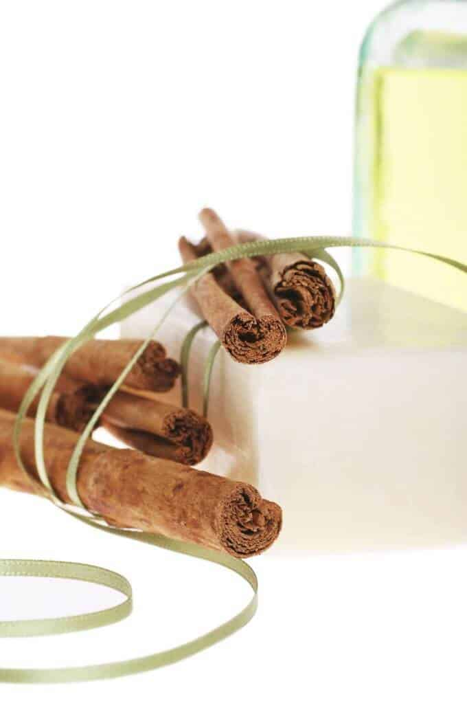 Photo of Cinnamon Essential Oil, cinnamon sticks and soap.