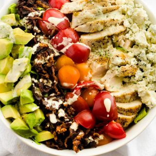 Square Overhead photo of a Avocado Grilled Chicken Salad in a white bowl drizzled with a creamy dressing.