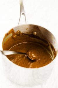 Photo of a mustard sauce in a saucepan against a white background.