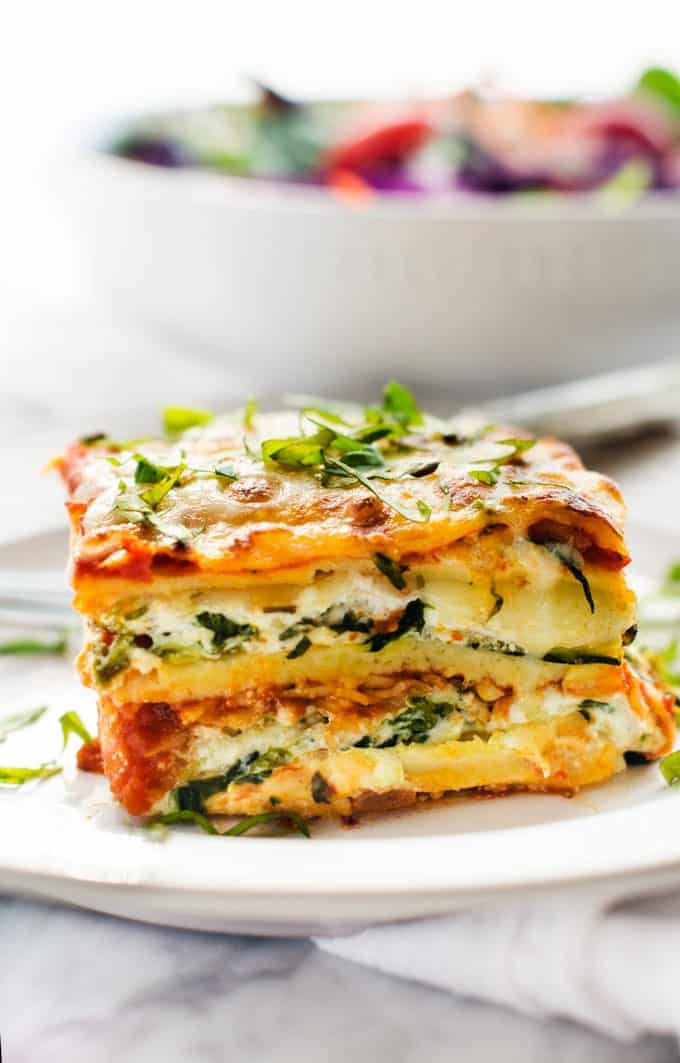 Side photo of gluten free vegetable lasagna garnished with basil sitting on a white plate with a salad behind it.