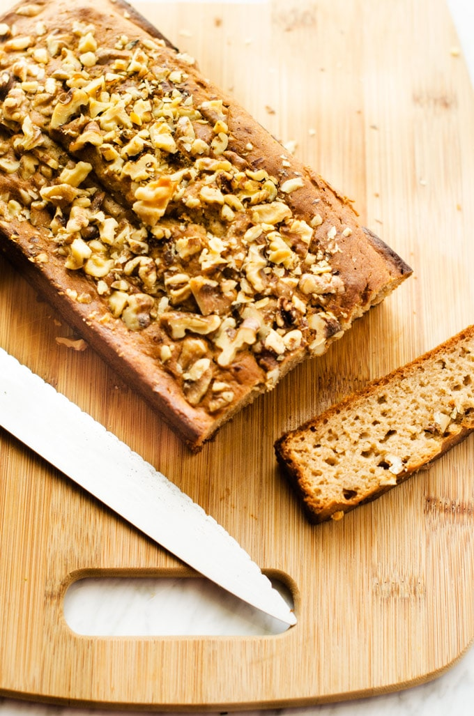 Photo of a loaf of Gluten Free Apple Bread on a cutting board with one slice cut out and a knife sitting next to it.