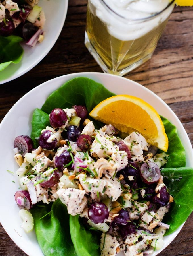 Overhead photo of Poppy Seed Chicken Salad on a bed of lettuces sitting on a white plate with an orange wedge next to it.
