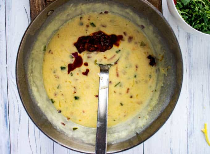 Photo of a cooked queso dip recipe with a chipotle chili pepper being added in.