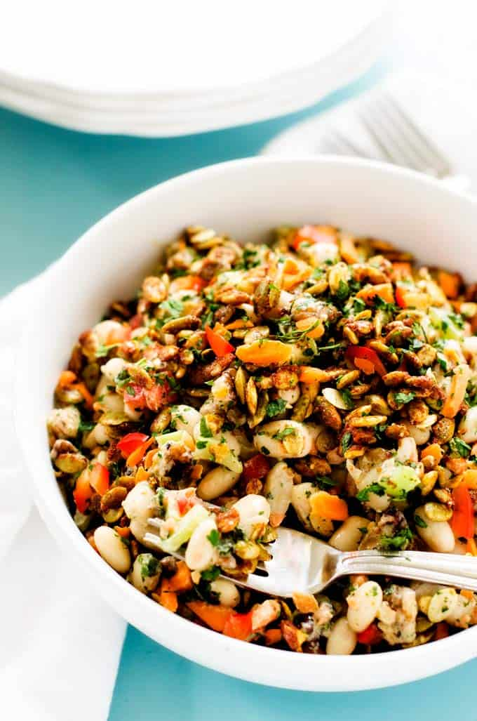 Photo of a prepared White Bean Salad Recipe in a white bowl with a forkful of salad.