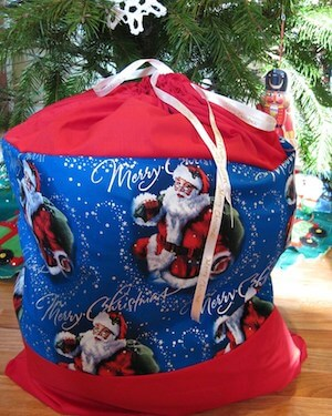 Photo of a DIY Santa Sack for toy donations sitting in front of a Christmas tree.