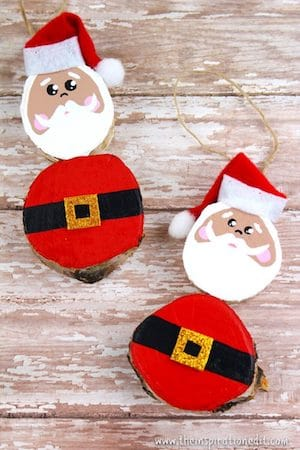 Photo of two wooden Santa crafts for kids on a white rustic background.