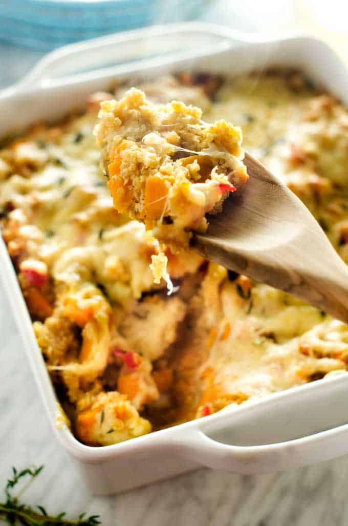 Photo of a spoonful of quinoa casserole piping hot from the oven over a casserole dish filled with sweet potato quinoa casserole.
