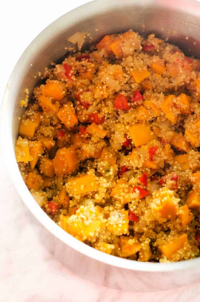 Process shot of a quinoa casserole being mixed in a bowl.