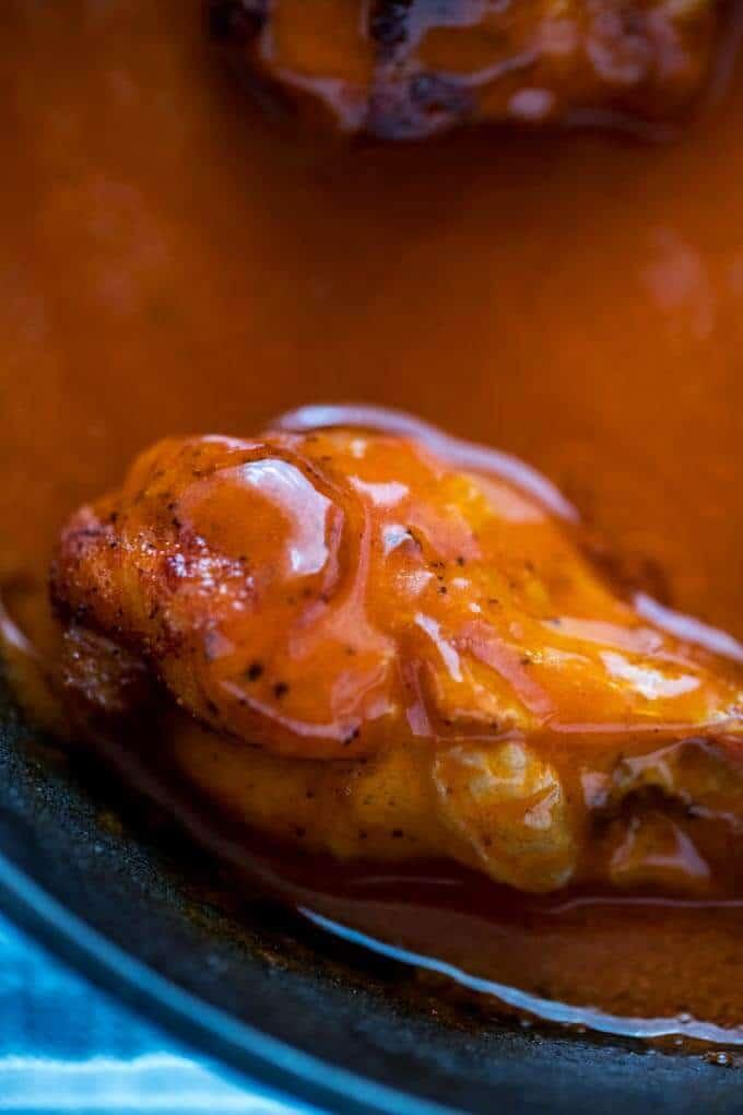 Close up photo of a baked chicken wing in buffalo sauce.
