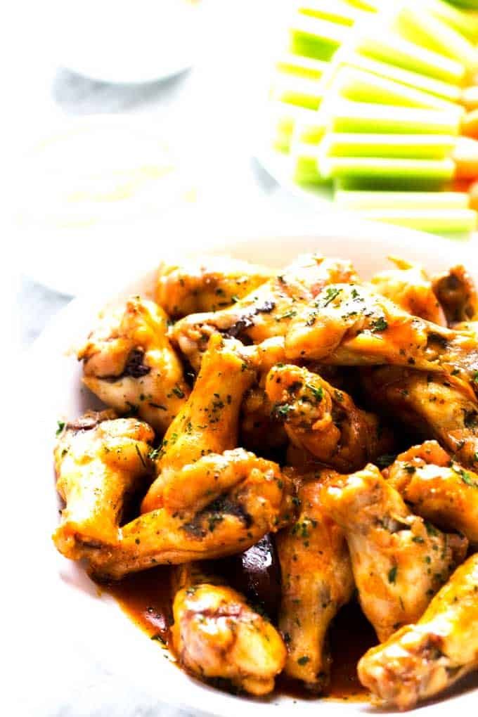 Photo of Healthy Chicken Wings on a white plate with vegetables behind them.