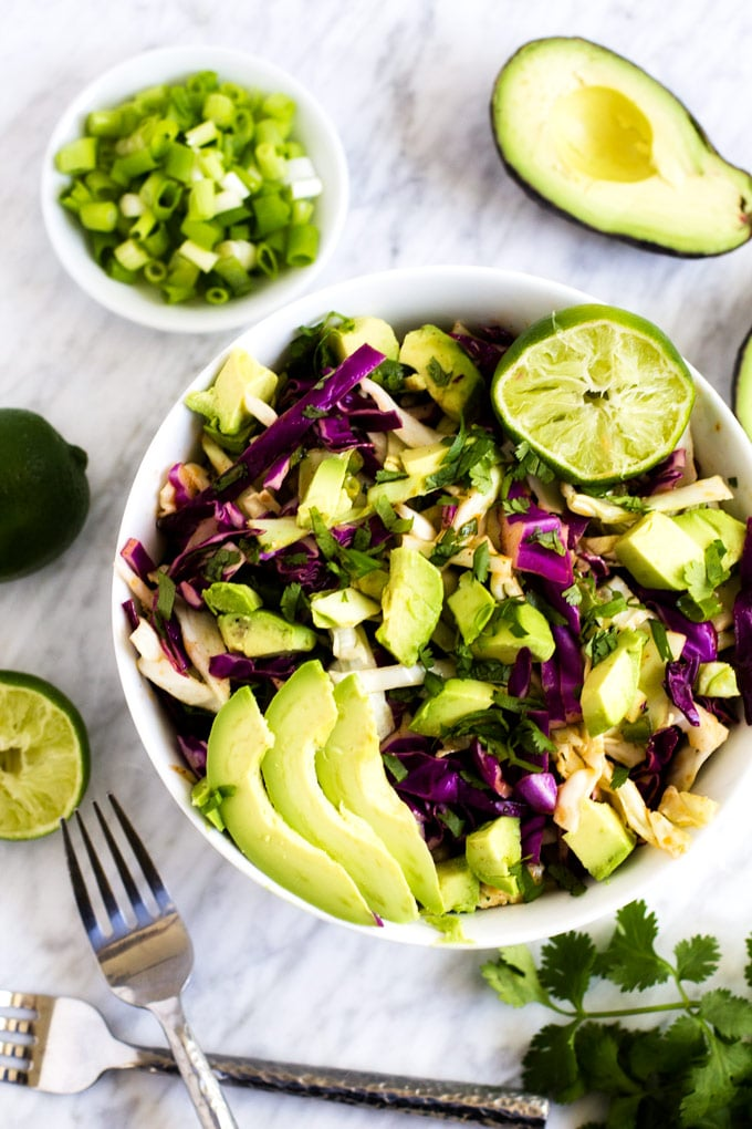 Overhead photo of a white bowl with Cilantro Lime Coleslaw in it surrounded by avocado, cilantro, limes, and green onions.