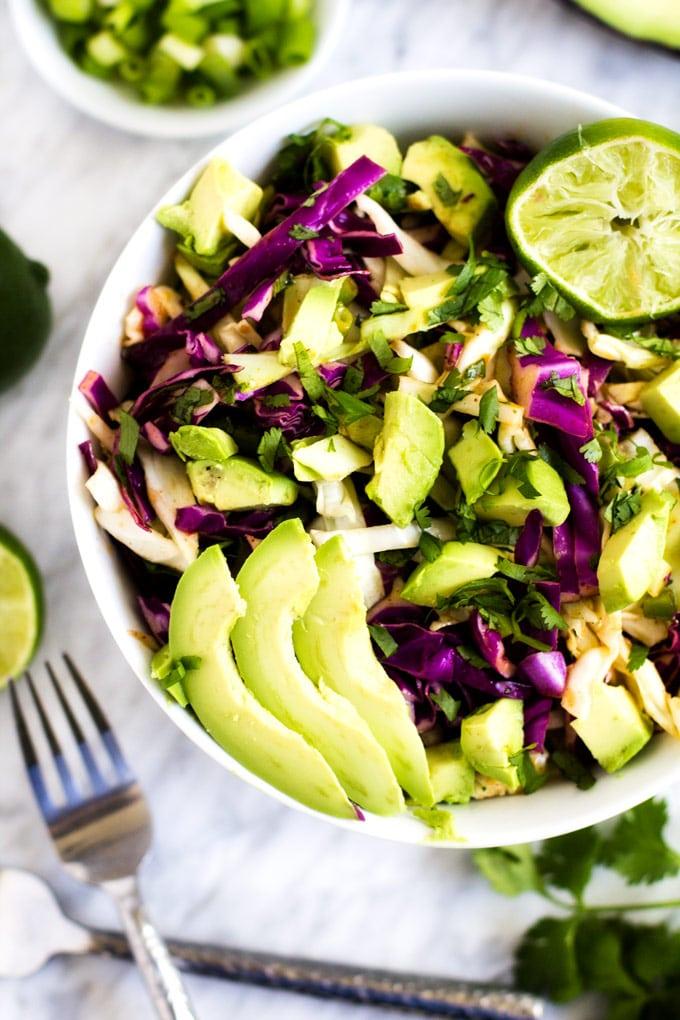 Overhead photo of an avocado cilantro slaw recipe in a white bowl.