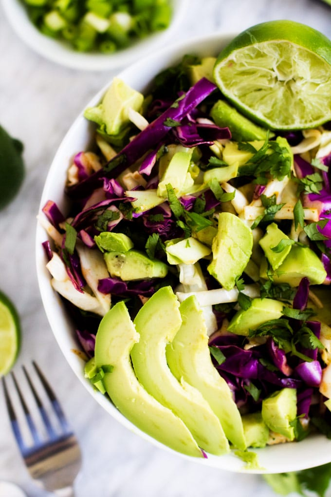 Close up overheat photo of a white bowl of Cilantro lime slaw garnished with avocado and a fresh squeezed lime.