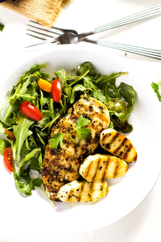 Overhead photo of a white plate with chicken and halloumi salad on a white background with two forks next to it.