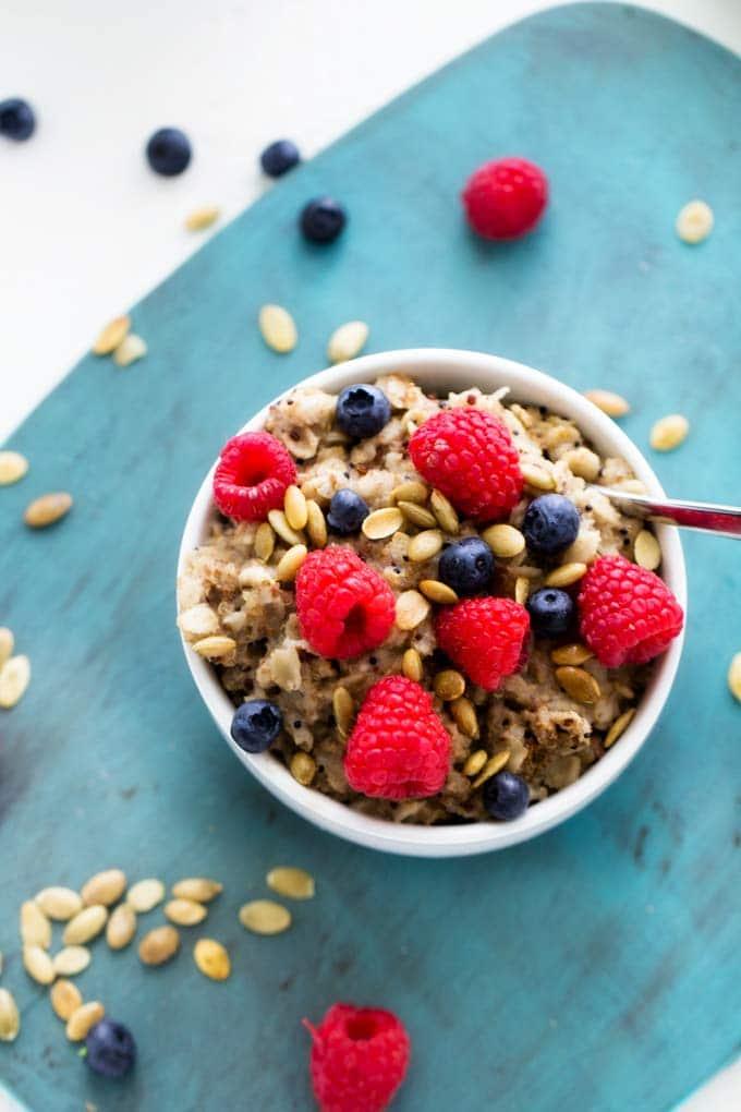 Close up shot of Quinoa & Oats Breakfast Bowl on a blue cutting board.