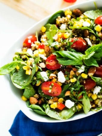 Close up image of a large white bowl with a quinoa corn salad in it sitting on a blue napkin.