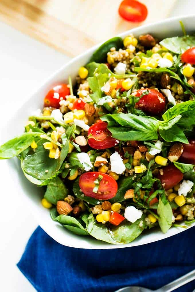 Close up image of a large white bowl with a quinoa corn salad in it sitting on a blue napkin. How To Make Quinoa Corn Salad (recipe)