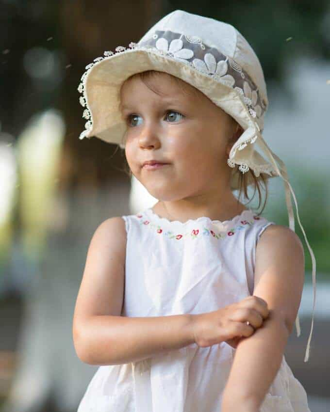 Photo of little girl in a white had scratching a bug bite - Essential Oils for Bug Bites