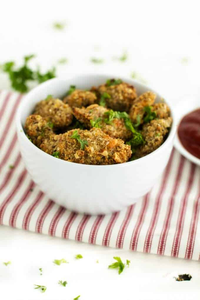 Photo of Healthy Chicken Nuggets in a white bowl garnished with parsley.