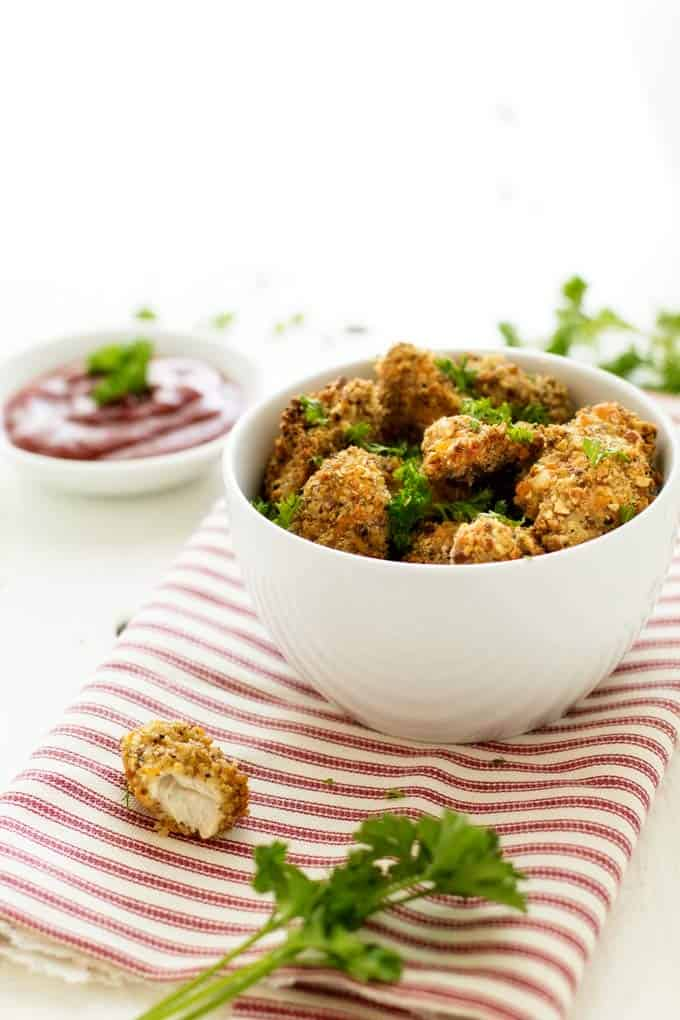 Photo of a bowl of Healthy Chicken Nuggets with one nugget that has a bite out of it sitting by the bowl.