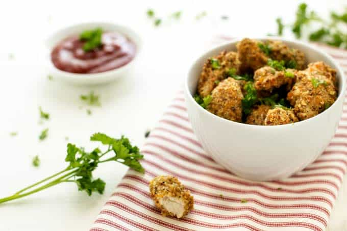 Horizontal image of Healthy Chicken Nuggets in a white bowl garnished with parsley.
