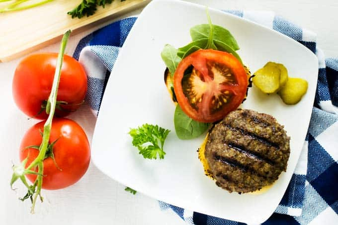 Horizontal image of healthy burgers with tomatoes sitting beside them.