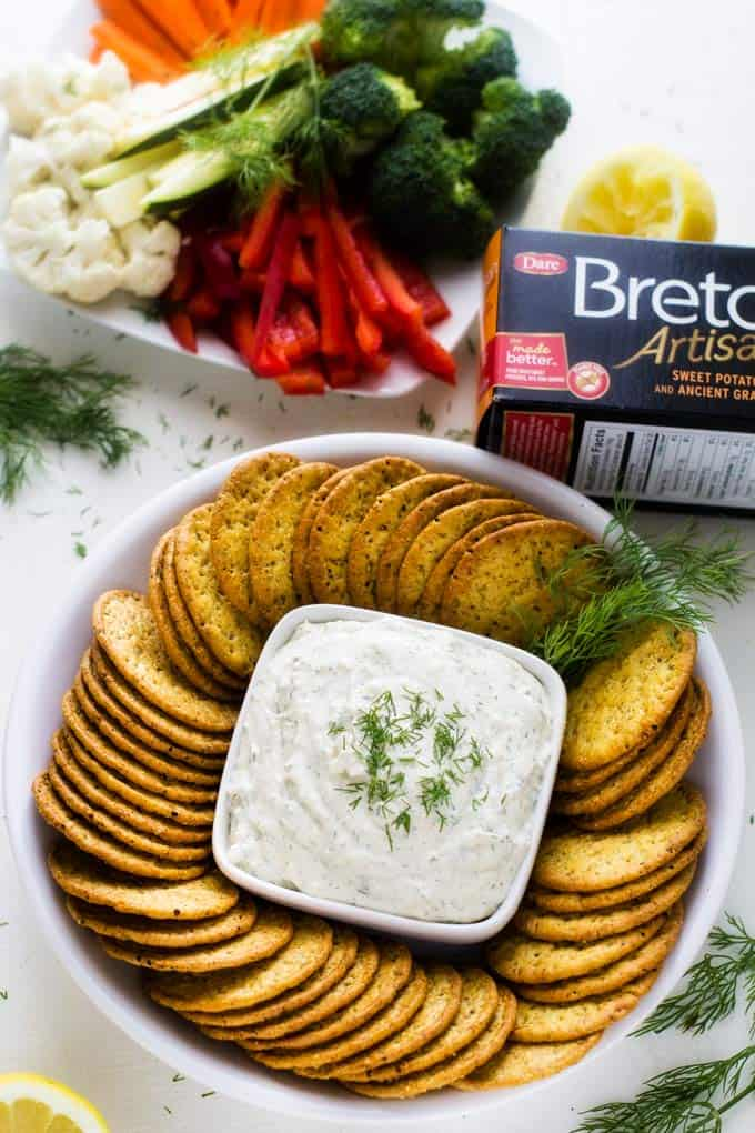 Horseradish Dill Schmear on a white plate with a box of Breton crackers.