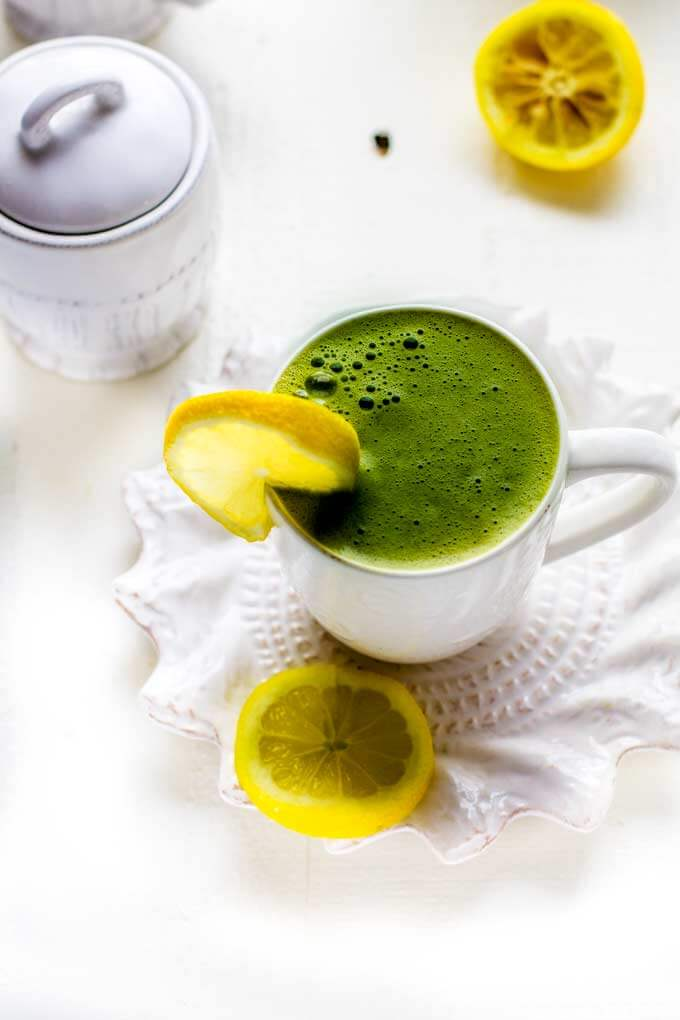 Matcha Green Tea Latte on a white saucer with lemon