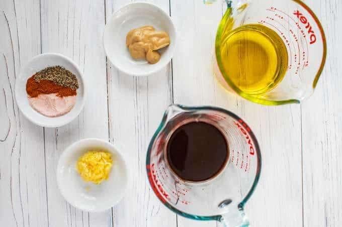 Photo of balsamic vinegar, olive oil, garlic, Dijon mustard, salt, pepper, and cayenne pepper in prep bowls