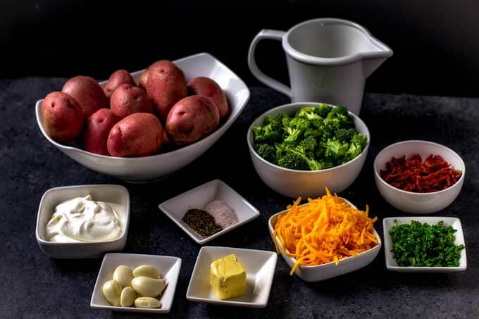 Cheesy Mashed Potatoes with Bacon and Broccoli in a white bowl with a black background.
