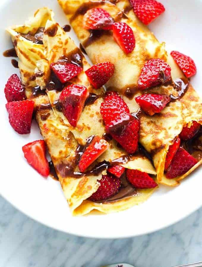 Overhead photo of gluten free crepes on a white plate with strawberries and chocolate hazelnut sauce on top.